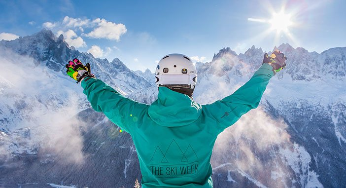 Person celebrating being on the ski week in front of mountainous landscape